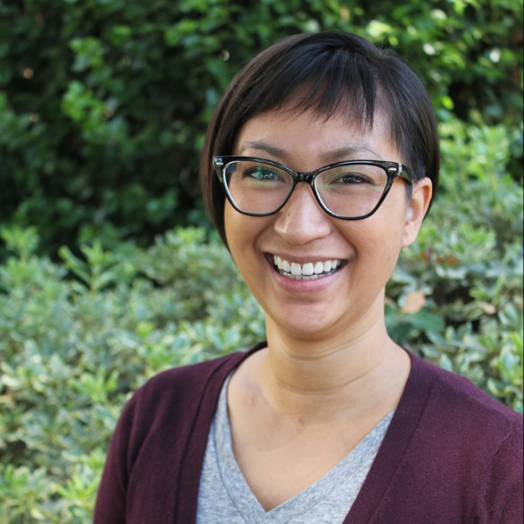 Image of Anne Cong-Huyen, Asian American woman with short hair, glasses, and a purple cardigan against a background of shrubberies
