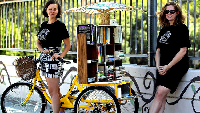 Two white women with a bookshelf on a custom yellow tricycle.